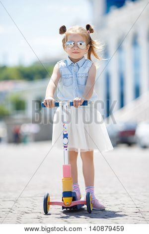 Little girl with blond hair,hair in two ponytails,in mirrored sun glasses,a light blue sleeveless shirt and white skirt, the one riding on the scooter in the city in the fresh air in summer