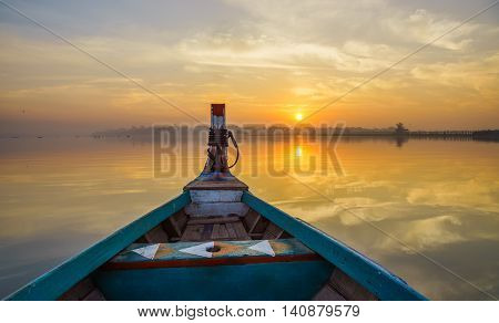 Wooden boat in Ubein Bridge at sunrise Mandalay Myanmar (World longest wooden bridge)