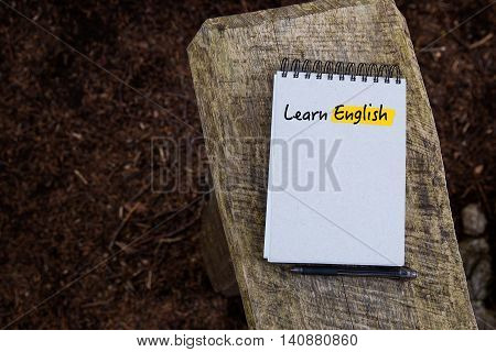 Learn English Text written on notebook page on the background of wood and forest texture