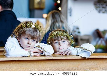 Two beautiful little kis in angel clothes for Christmas story in a church. Happy adorable blond children, boys singing and excited about holiday.