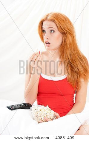 Portrait of surprised beautiful girl open-mouthed watching movie or tv in bed and eating popcorn