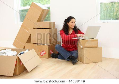 Mulher com o laptop em casa nova