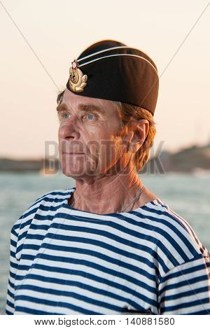 man standing in garrison cap and striped vest on a background of sea summer day