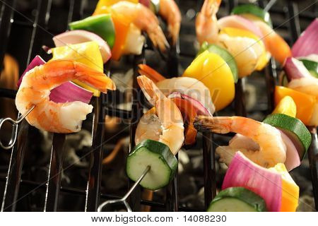 Shrimp and vegetable skewers cooking on grill
