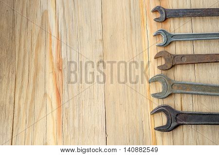 Old work tools spanner wrench on a wooden table. Top view with empty space