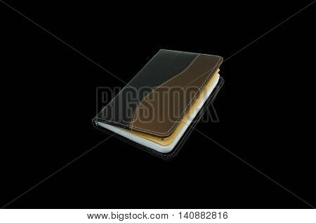 Notebook for writing notes isolated on black background.