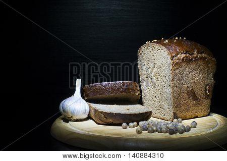 Rural concepts. Dark rye bread allspice and garlic on black.