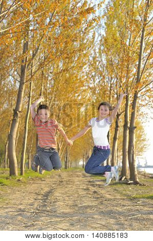 Happy active children jumping in forest, close up