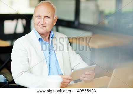 Senior man sitting at cafe with digital tablet