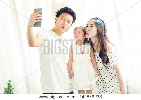 Family With Little Girl In Park Taking Selfie By Mobile Phone.