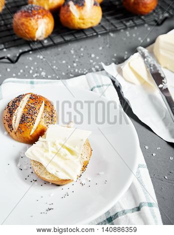 Homemade baked sliced pretzel bun with poppy seeds and butter on it on white plate. Pretzel bun is german cuisine dish, ideal for lunch or breakfest with butter and tea.