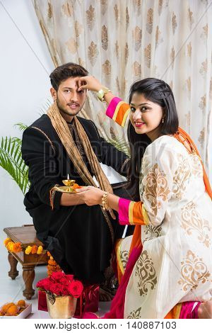 indian sister applying tika on brother's forehead, enjoying and celebrating Raksha Bandhan festival