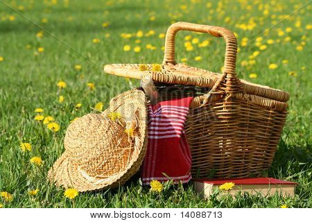 Picnic basket and straw hay laying on the grass