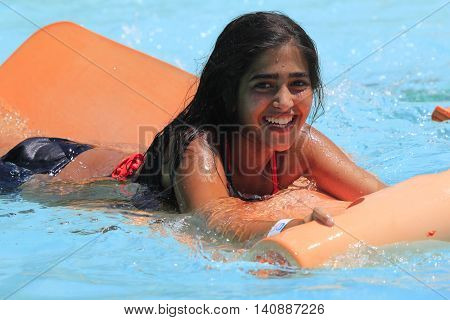 Rhodes  Greece-July 30 2016: The girl joying after mat racer slide.Mat racer slide is very popular for young people in the Water Park.Water Water Park is located on the island of Rhodes in Greece and one of the most largest in Europe and is a very popular