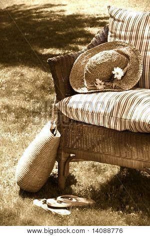 Grass lawn with a wicker chair on a hot summer's day/ Sepia tone