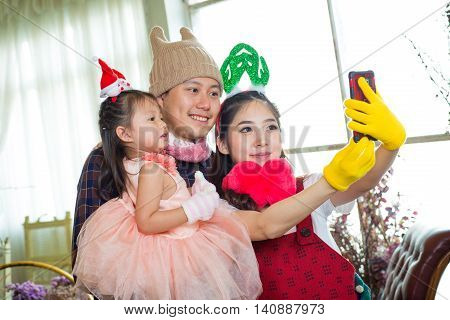 Family With Little Girl In Garden Taking Selfie By Mobile Phone.
