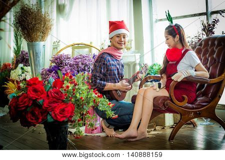 Love, Wedding, Winter, Dating And People Concept - Smiling Couple In Play Ukulele.