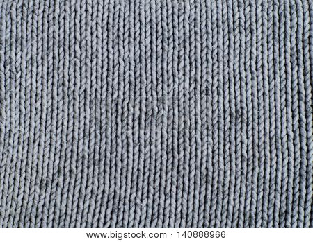 Knitted gray wool pattern close up. Texture of knitting the front embroidery.