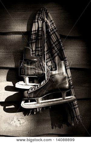 Old hockey skates with scarf hanging on a wall/ BW filter