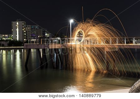 Steel Wool spinning sideways over a jetty into the water