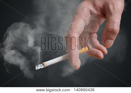 Man (smoker) Is Holding Cigarette In Hand On Black Background. S