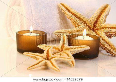 Pequeñas velas marrones, toalla y estrellas de mar con un cálido resplandor