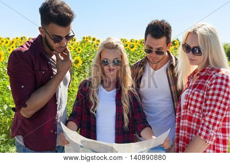 People group looking road map standing sunflowers field outdoor two couple summer day holiday trip