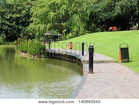 a beautiful park with a lake and a green lawn