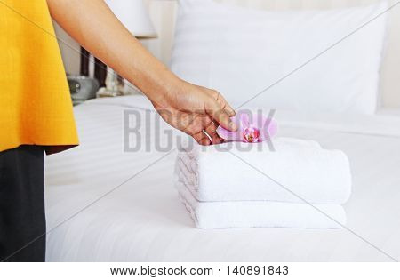 Maid doing room service in hotel, she is making up the bed