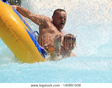 Rhodes Greece-July 30 2016: father and son on the rafting slide in the Water park.Rafting slide is one of many popular game for adults and children in park.Water Water Park is located on the island of Rhodes in Greece and one of the largest.
