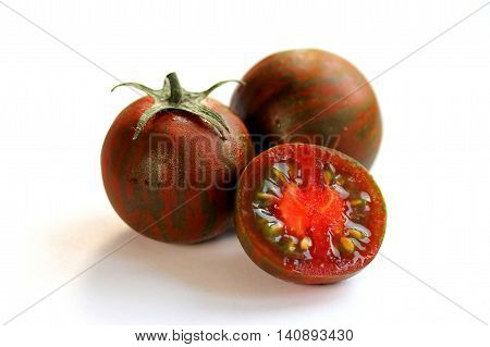 Black kumato tomatoes on a white background