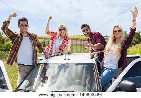 Excited friends on car roof outdoor countryside raise arms people smile holding hands up summer day trip