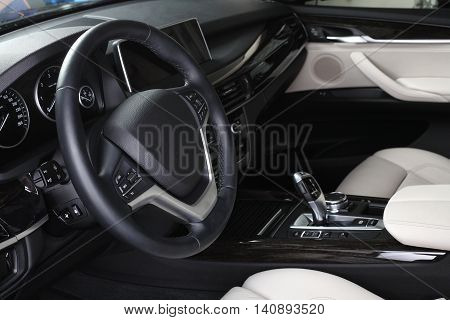 Interior of leather passenger compartment of the car in light-dark tones.