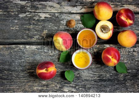 Fresh ripe apricots and apricot oil on old wooden background top view