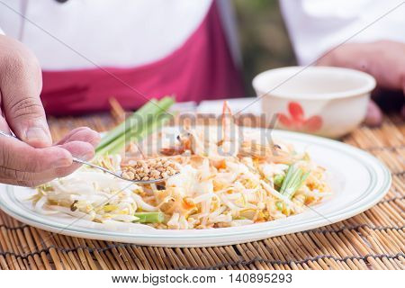 Chef decorated Pad Thai Menu with minced Peanut bean / cooking Pad Thai concept