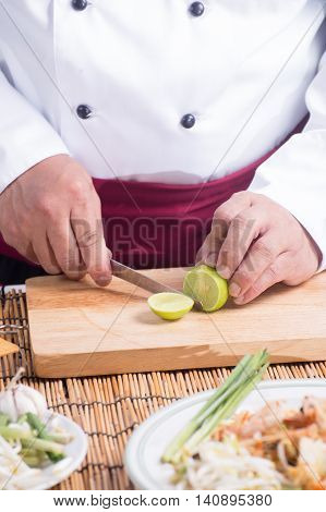 Chef slicing Lime for decorated Pad Thai / cooking Pad Thai concept