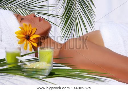 Pretty asian woman relaxing at a spa with white background