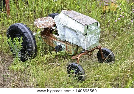 An old homemade pedal tractor in the long grass is lacking a steering wheel