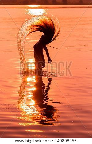 Silhouette of young girl in the water splashing their hair