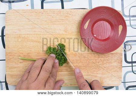 Cutting parsley on a board before cooking / cooking sausage bread concept