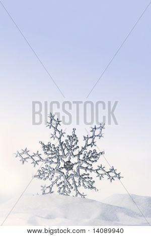 Sparkling snowflake in the snow with white background