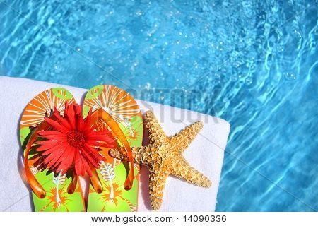 Colorful sandals with flower and white towel by the pool