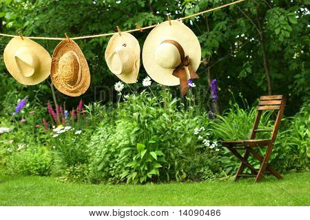 Summer straw hats hanging on old clothesline