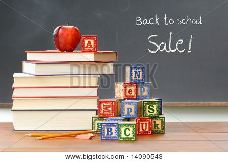 Pile of books with wooden blocks in front of chalkboard