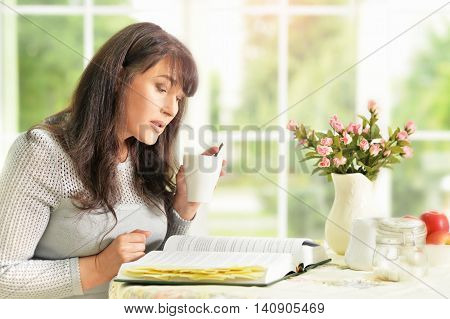 happy Senior woman reading a book with tea