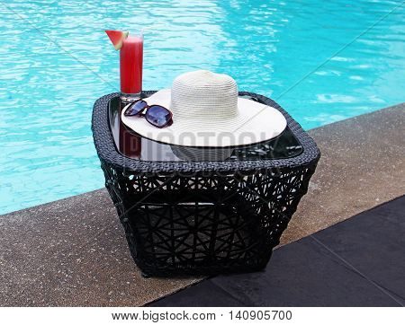 hat with sun glasses and watermelon juice poolside
