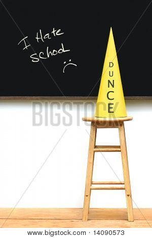 Yellow dunce hat on stool with chalkboard