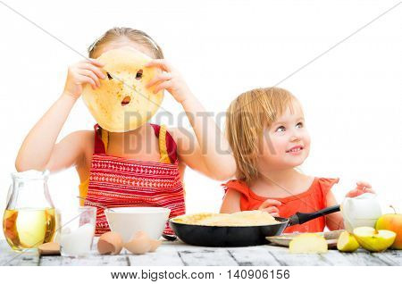 funny sisters cooking pancakes on kitchen isolated on a white background