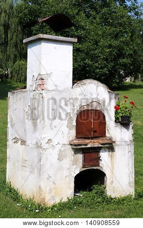 Rustic hundred years old hungarian furnace against green natural background in rural village garden.Traditional fireplace oven for cooking baking