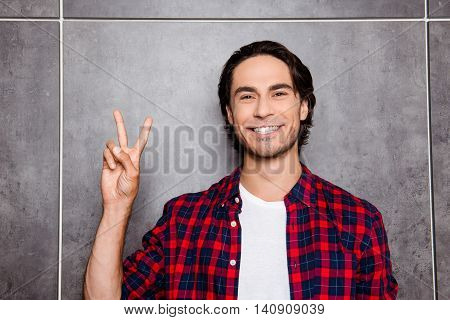 Happy Young Man  With Beaming Smile Showing Two Fingers